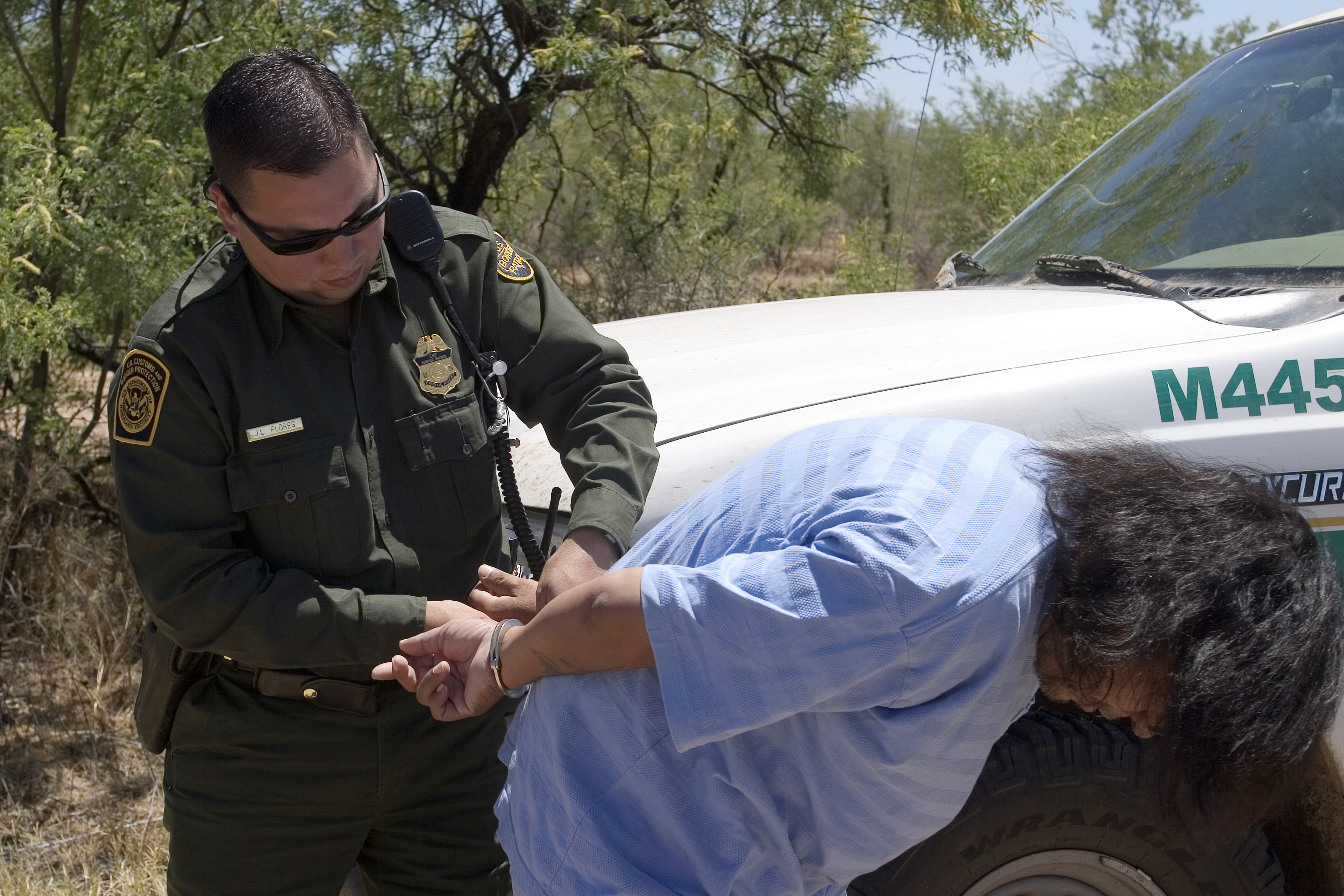 Border Patrol agent places a Mexican National under arrest for transporting drugs into the U.S.